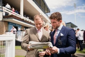 Couples enjoying a day at the races. Two males looking at a newspaper at the races.